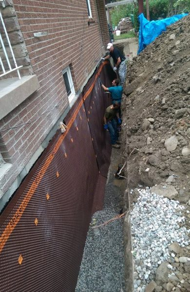 men in a trench waterproofing a basement